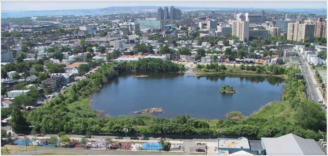 Arial photo of Jersey City Reservoir #3 on a sunny day with trees in full green bloom and the lake deep blue-green